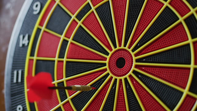 close up of a dartboard in a sports bar; several darts hit the board. - dart board stock videos & royalty-free footage