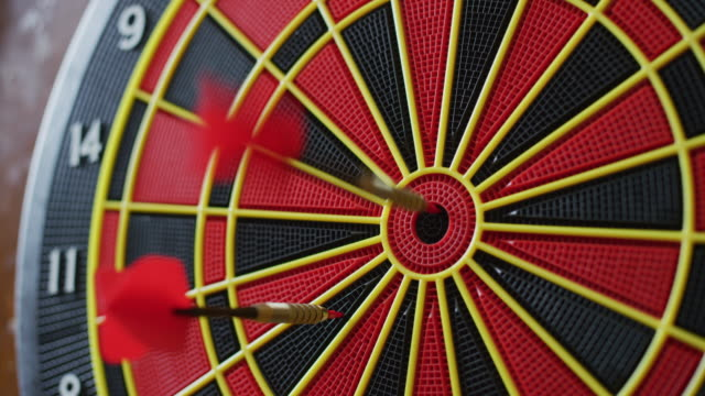 close up of a dartboard in a sports bar; several darts hit the board, one dart hits the bullseye! - darts stock videos and b-roll footage