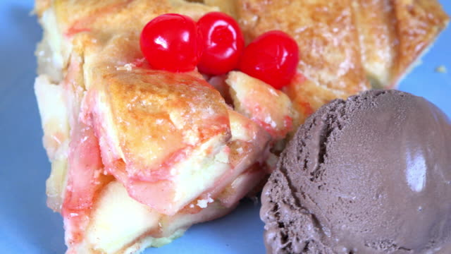 Close up of a dessert containing apple pie and chocolate ice cream