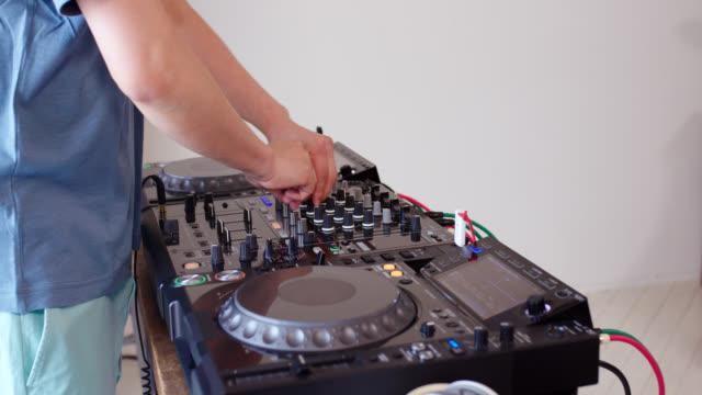 vídeos de stock e filmes b-roll de close up of a dj practicing with a sound mixer at home - dj