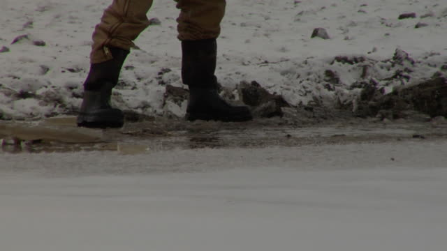 stockvideo's en b-roll-footage met close up of a farmer's feet wearing rubber boots, chopping out the ice in a pond so his cattle herd will have water in the winter. - rubber