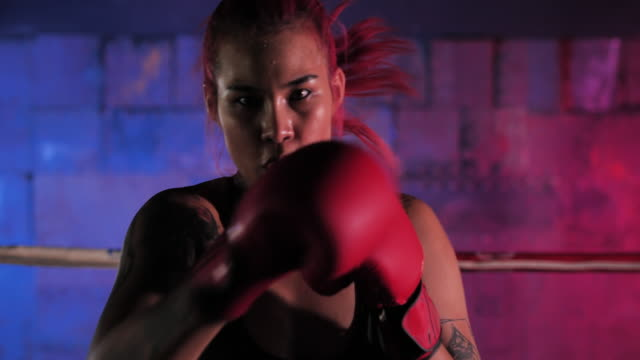 close up of a female boxer punching inside a boxing ring.women on boxing training.sport - coaching - glove fist stock videos & royalty-free footage