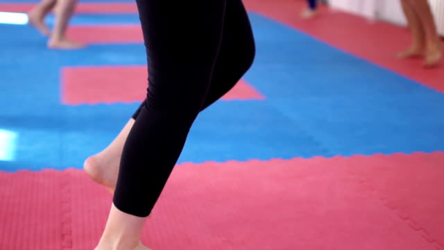 close up of a female in a gym warming up in slow motion - barefoot stock videos & royalty-free footage