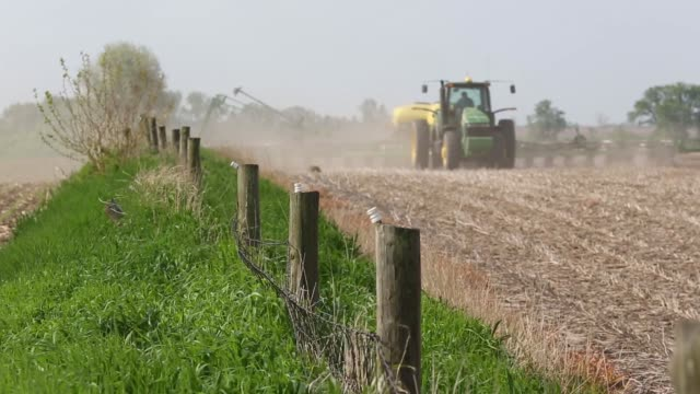 Close up of a fence as a John Deere tractor pulls a planter planting nonGMO seed corn in background in Malden Illinois US on Tuesday May 17 2017