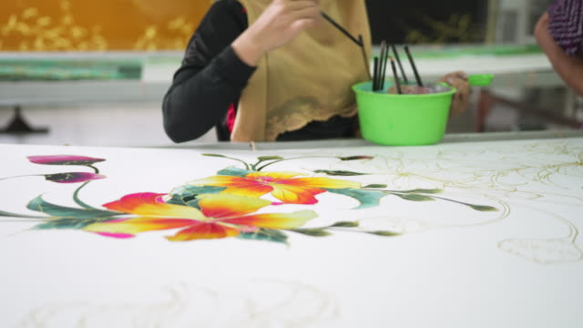 Close up of a flower being coloured on batik