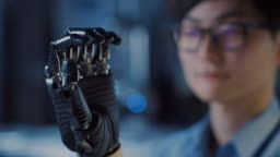 Close Up of a Futuristic Prosthetic Robot Arm Being Tested by a Professional Development Engineer in a High Tech Research Laboratory with Modern Computer Equipment.
