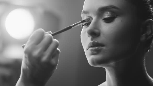 näring av ett tjej ansikte. en make-up artist applicerar skugga till aktrisögonlocken med en sminkborste på uppsättningen. svartvit video. - skådespelerska bildbanksvideor och videomaterial från bakom kulisserna
