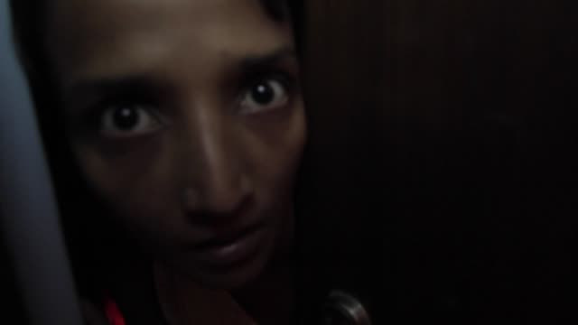 close up of a girl peeping from behind her door in a state of fear to check whats going on outside - ajar stock videos & royalty-free footage