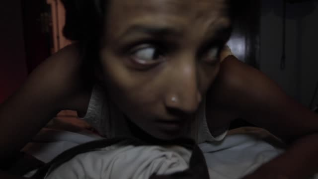 Close up of a girl with short hair, terrified out of her wit, crawling onto her bed and towards the camera