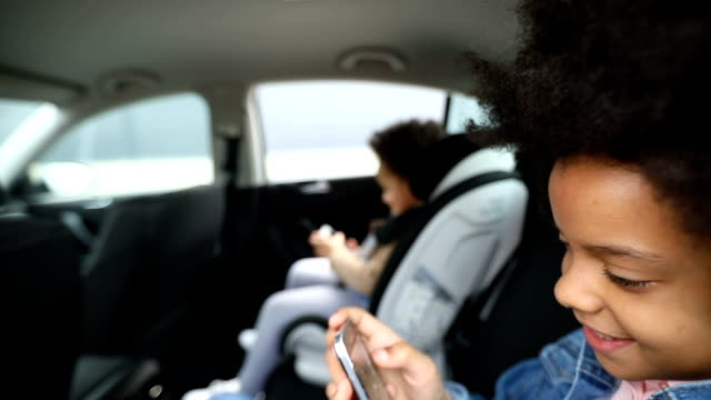 close up of a girls using smart phones in back seat of car - back seat stock videos & royalty-free footage