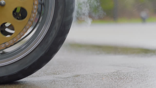slo mo. cu. close up of a gold stunt motorcycle wheel on wet pavement in an empty parking lot - motorcycle racing stock videos and b-roll footage
