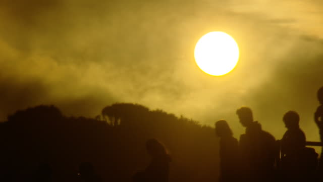 close up of a golden sun starting to set as misty clouds pass in front silhouette of anonymous tourists walk through shot - ecoturismo video stock e b–roll