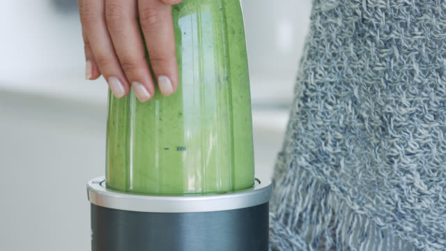 close up of a green juice being made in a blender - urbanlip stock videos & royalty-free footage