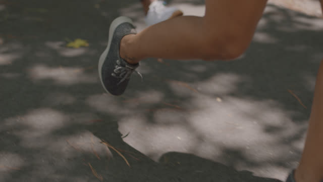 vídeos y material grabado en eventos de stock de slow mo. cu. close up of a group of athletic women's feet running on a path in the forest - pantalón corto