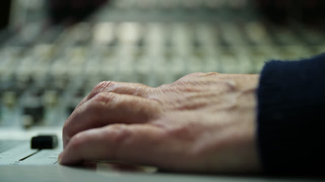 vídeos de stock e filmes b-roll de close up of a hand adjusting a channel fader on a sound mixing desk - disco audio analógico