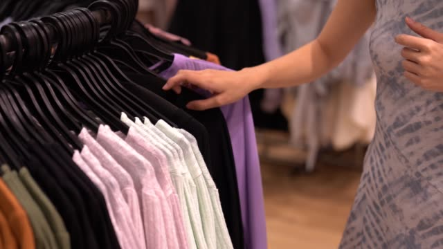 close up of a hand arranging clothing at clothing store - pendere video stock e b–roll