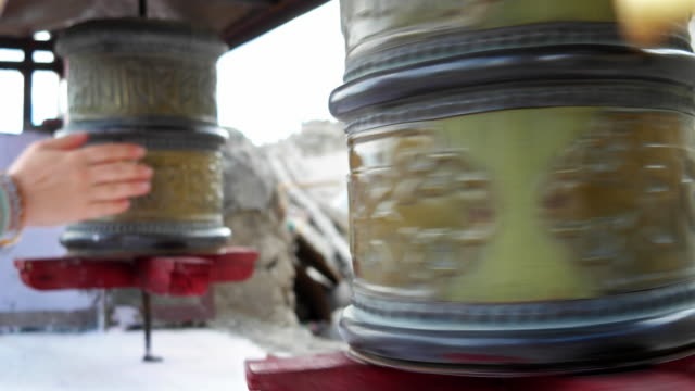 Close up of a hand moving the Buddhist prayer wheels at a Buddhist monastery in Ladakh