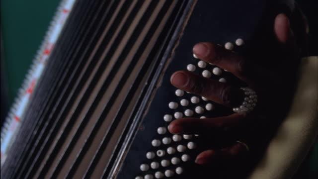 vídeos de stock e filmes b-roll de close up of a hand playing an accordion - acordeão instrumento