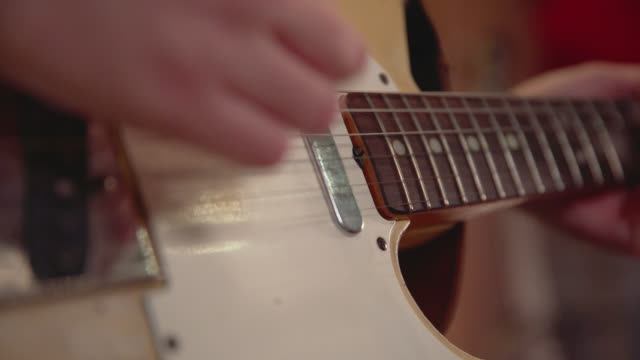 close up of a hand strumming an electric guitar - solo performance stock videos and b-roll footage