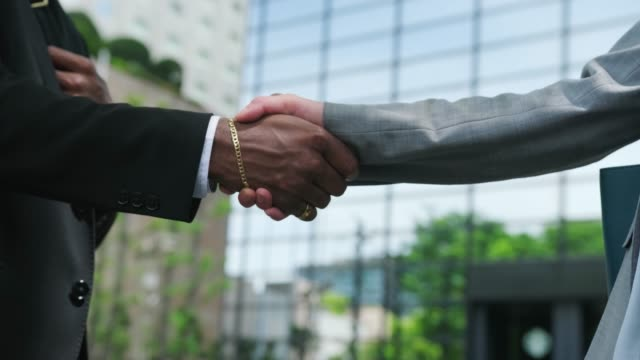 close up of a handshake between an african american businessman and japanese business woman outdoors - handshake stock videos & royalty-free footage