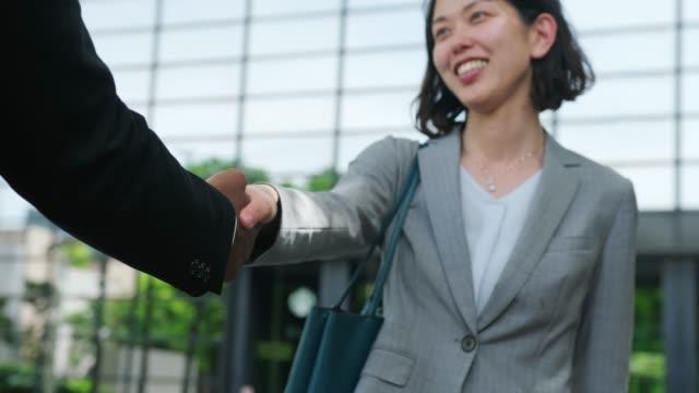 アフリカ系アメリカ人のビジネスマンと日本のビジネスウーマンの間の握手のクローズアップ - ホワイトカラー点の映像素材/bロール