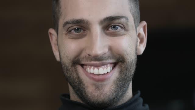 vídeos de stock, filmes e b-roll de feche acima de um homem novo feliz que sorri na câmera - brasileiro pardo
