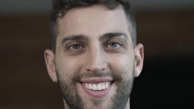 nahaufnahme eines glücklichen jungen mannes, der lächelt in die kamera - vollbart stock-videos und b-roll-filmmaterial