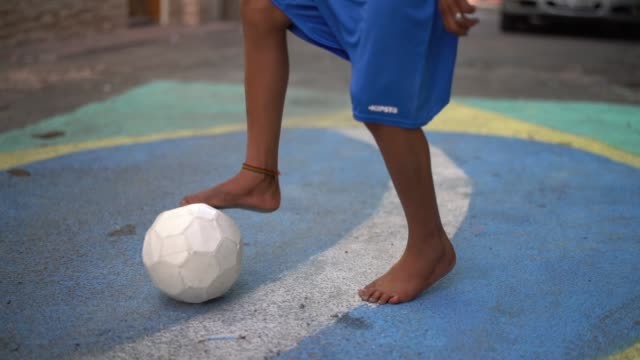 vídeos de stock e filmes b-roll de close up of a kid playing soccer in the street - football