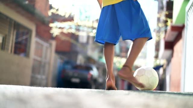 nahaufnahme von einem kind spielen fußball auf der straße - barfuß stock-videos und b-roll-filmmaterial
