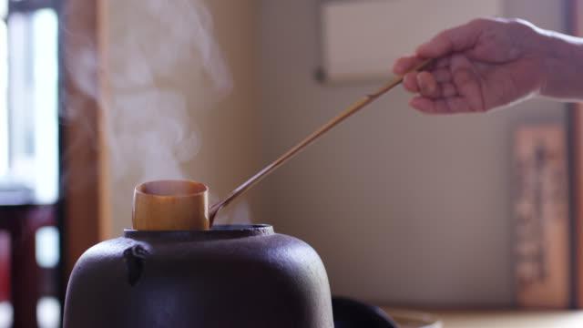 vídeos y material grabado en eventos de stock de el cierre de un cucharón que extrae agua caliente de una olla tradicional japonesa - sado