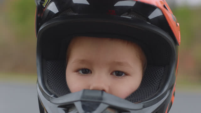 slo mo. cu. close up of a little boy taking off his helmet and looking straight into the camera and bites his lip in a parking lot - 取り除く点の映像素材/bロール