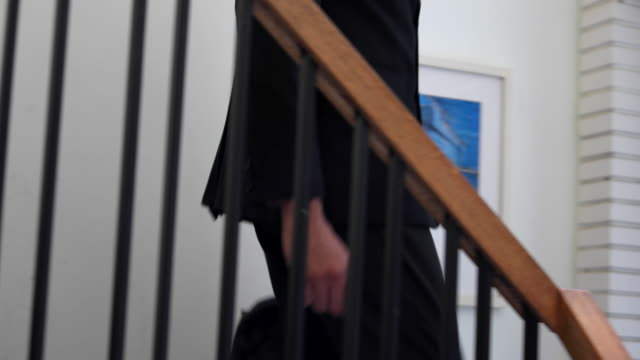 close up of a man coming down steps and existing the house for office - staircase video stock e b–roll