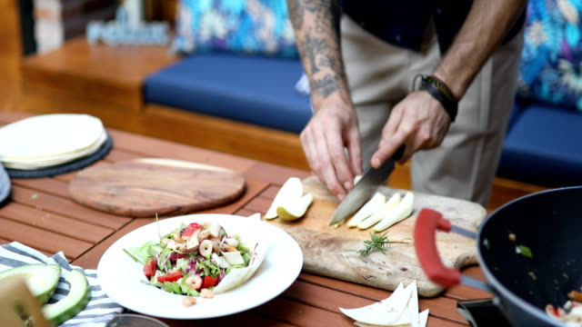 Close up of a man decorating salad with pear