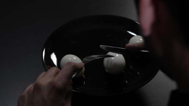 vídeos y material grabado en eventos de stock de close up of a man man eating boiled eggs on a black plate in a dark dining room - modales de mesa