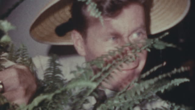 close up of a man wearing a floral straw hat and posing behind some fern leaves; he tries to bite a hands with big blue ring in front of him - straw hat stock videos & royalty-free footage