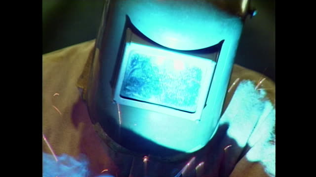close up of a man welding with a protective helmet inside at the railex corp which manufactures clothing racks for dry cleaners. - welding helmet stock videos & royalty-free footage