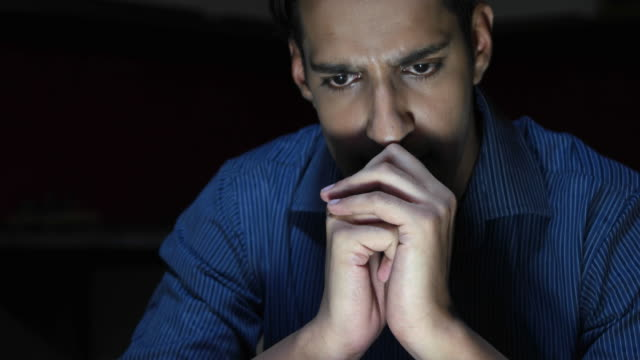 Close up of a man working late night on his computer to come to a solution of a deep problems that bothers him after the bad news