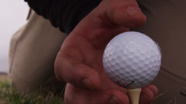 vidéos et rushes de close up of a man's dirty fingers placing a golf ball on a tee. - positionner