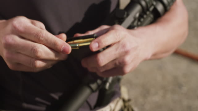 Close up of a man's hands loading bullets, rounds of ammunition into the clip of a rifle