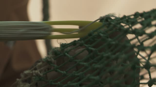 Close up of a man's hands repairing fishing net indoor in Sicily