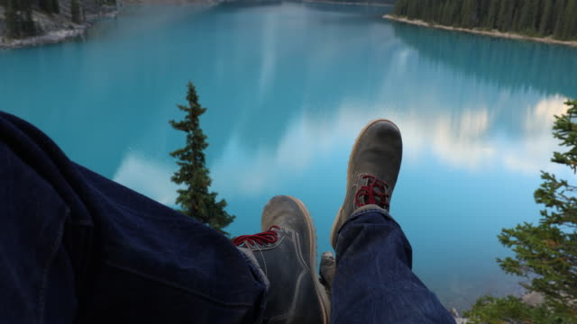 A close up of a man's leather boots with red shoelaces in front of the turquoise waters of Moraine Lake.
