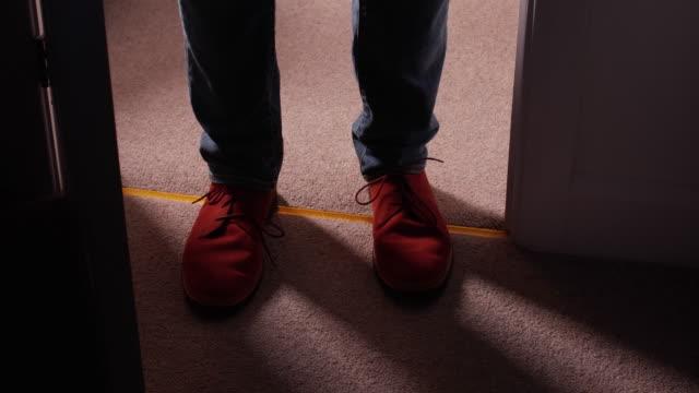 vidéos et rushes de fermez-vous vers le haut des chaussures de port d'un homme entrant dans une pièce foncée. - salle attente