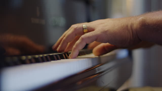 Close up of a married man's hands at the keyboard of a piano.