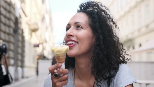 close up of a mature hispanic woman with afro eating ice cream on the streets of budapest - gelato stock videos & royalty-free footage