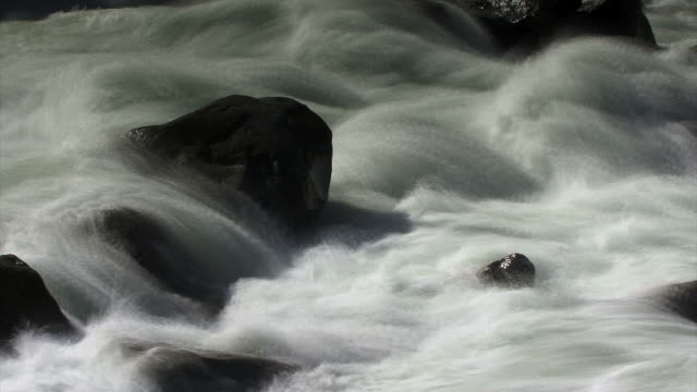 close up of a misty, foamy river roaring over rocks. - digital enhancement stock videos and b-roll footage