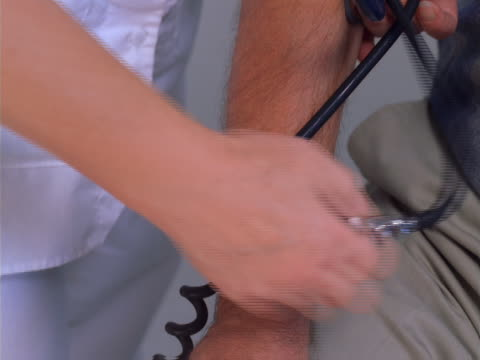 stockvideo's en b-roll-footage met close up of a nurse's hands as she takes a man's blood pressure - artbeats