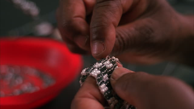 close up of a pair of hands beading with a needle and thread - perlenschnur stock-videos und b-roll-filmmaterial