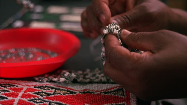 close up of a pair of hands beading with a needle and thread with some completed beadwork on the table - bead stock videos & royalty-free footage