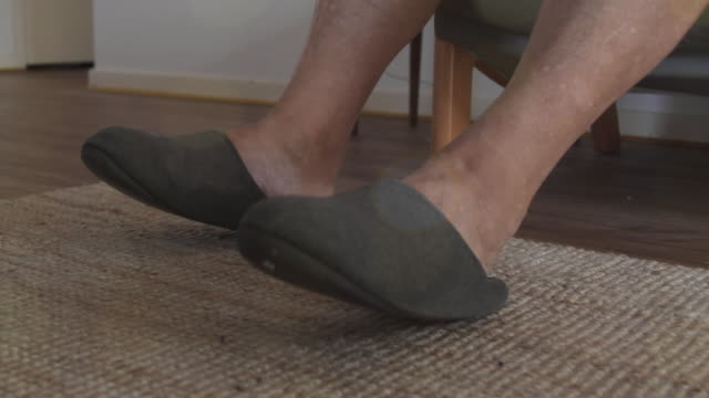 close up of a pair of older mans feet with slippers tapping - slipper stock videos and b-roll footage