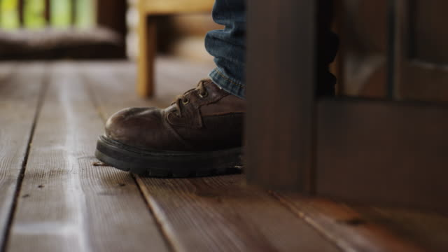 Close up of a porch door, it opens and a man in work boots and jeans step outside to go to work on the farm